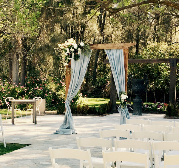 rustic wooden 2 post structure with dusty blue natural linen draping